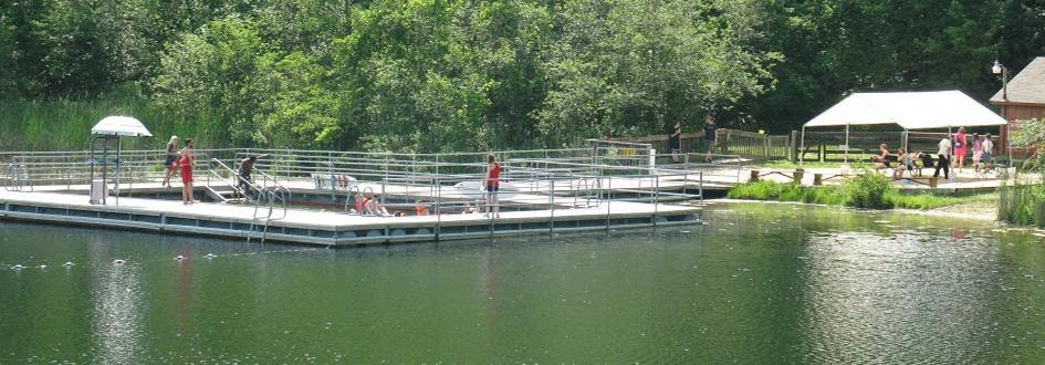 Several lifeguards stand on a large wooden dock lined with metal railings and a small pool in the center. Adults and children sit on picnic benches under a white tent on shore.