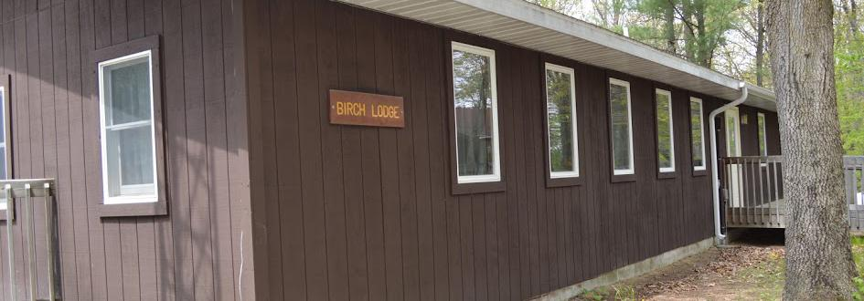"""The side of a brown building with a sign on it that says """"Birch Lodge."""""""