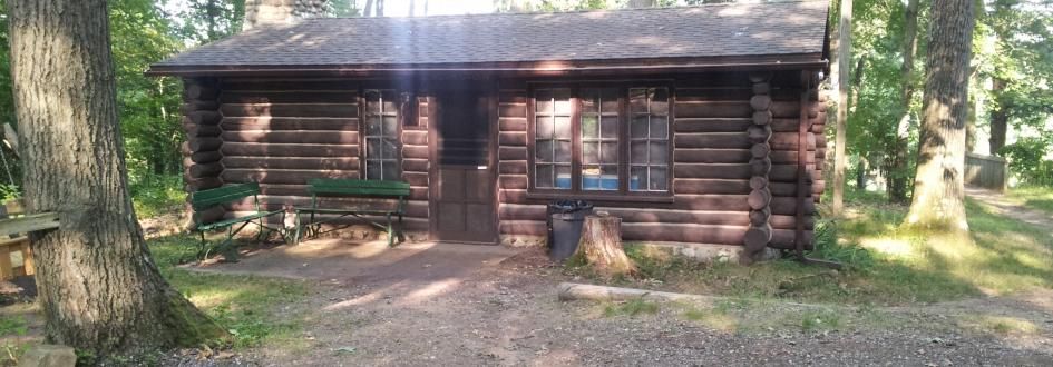 Roth Cabin with two green benches out front.