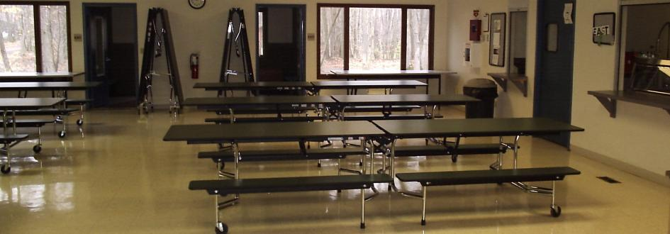 Several rows of tables line a cafeteria.
