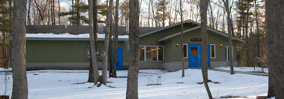 White Pine lodge exterior surrounded by snow. The green building has bright blue doors.